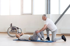 Kindly general practitioner stretching the handicapped in the gym Stock Photography
