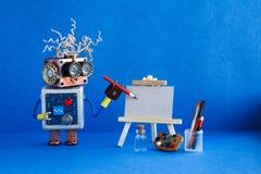 Kindly Roboterkünstler fängt an, eine Zeichnung mit einem Bleistift herzustellen Weißbuchschablone, hölzernes Gestell und Künstle Lizenzfreies Stockfoto