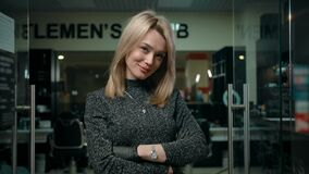 Kindly smiling female turning head for camera in modern barbershop