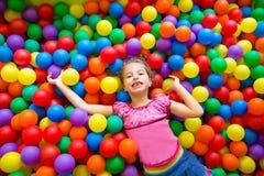 Kindmädchen auf hoher Ansicht des bunten Kugelspielplatzes Stockfotografie