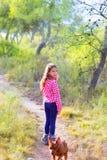 Kindmädchen, das in den Kieferwald mit Hund geht Stockfotografie