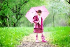 Kindmädchen, das draußen mit rosafarbenem Regenschirm aufwirft Lizenzfreie Stockfotos