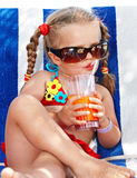 Kindmädchen in den Gläsern und roter Bikini trinken Saft. Stockfotografie
