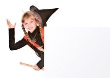 Kindmädchen im Halloween-Hexekostüm mit Fahne. Stockfotografie