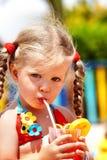 Kindmädchen im Orangensaft des roten Bikinigetränks. Lizenzfreies Stockbild