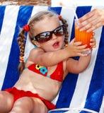 Kindmädchen im roten Bikinigetränksaft. Stockfoto
