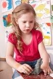 Kindmädchenform vom Lehm im Spielraum. Stockbild