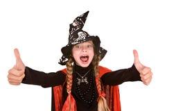 Kindmädchenhexe im schwarzen Kostüm mit dem Daumen. Lizenzfreies Stockfoto