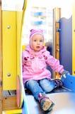 Kindmädchen, das auf Plättchen sitzt Lizenzfreie Stockfotografie