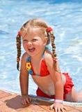 Kindmädchen im roten Bikini nahe blauem Swimmingpool. Stockbilder