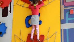 Kindmeisje die omhoog op een binnen het beklimmen muur beklimmen De sportenspelen van de kinderen van babyspelen op de speelplaat stock video