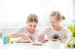 Kindmeisje die Pasen-koekjes verfraaien royalty-vrije stock fotografie