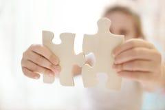 Kindmeisje die twee grote houten raadselstukken houden Overhandigt verbindende puzzel Sluit omhoog foto met kleine dof Royalty-vrije Stock Fotografie