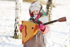Kindmeisje in een bontjas en een sjaal in Rus met een balalaika stock afbeelding
