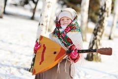 Kindmeisje in een bontjas en een sjaal in Rus met een balalaika stock foto