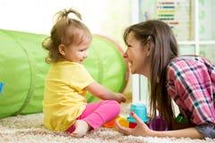 Kindmeisje en haar moeder die samen met speelgoed spelen Royalty-vrije Stock Afbeelding