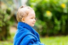Kindmeisje in handdoek na zwemmen die in zon bij de tropische toevlucht zonnebaden Royalty-vrije Stock Foto