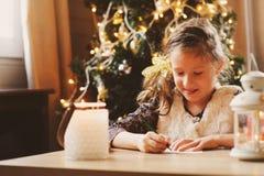 Kindmeisje het schrijven brief aan Kerstman thuis 8 jaar oud meisjes diegiftlijst thuis maken voor Kerstmis of Nieuwjaar Royalty-vrije Stock Foto