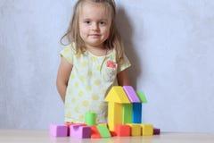 Kindmeisje het spelen aannemersspeelgoed thuis stock afbeelding