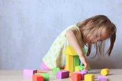 Kindmeisje het spelen aannemersspeelgoed thuis stock afbeeldingen