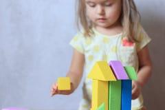 Kindmeisje het spelen aannemersspeelgoed thuis stock fotografie