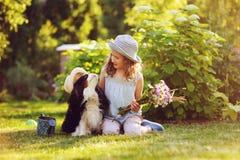 Kindmeisje het spelen met haar spanielhond in de zomertuin, allebei die grappige tuinmanhoeden dragen, die boeket houden royalty-vrije stock foto