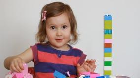 Kindmeisje het spelen met kleurrijke blokken van een aannemer stock footage