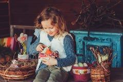 Kindmeisje het spelen met paaseieren en met de hand gemaakte decoratie in comfortabel buitenhuis Royalty-vrije Stock Fotografie