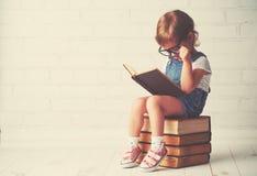 Kindmeisje met glazen lezen boeken Stock Afbeeldingen