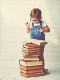 Kindmeisje met glazen lezen boeken Stock Afbeelding