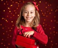 Kindmeisje met Kerstmis huidig op donkerrood met lichten Stock Afbeelding