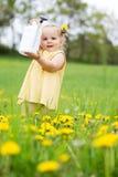Kindmeisje tussen paardebloemen Royalty-vrije Stock Fotografie