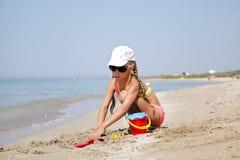 Kindmeisje in zand dichtbij het overzees stock fotografie