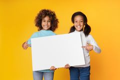 Kindmeisjes die lege banner voor uw tekst houden stock afbeelding