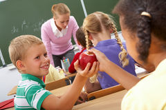 Kindness. Portrait of schoolgirl passing red apple to classmate during lesson