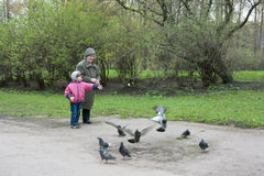 Kindness lesson. Granddaughter and grandmother are feeding pigeons Royalty Free Stock Image