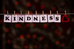 Kindness text on papers with clothespins with garland bokeh on background. The word `Kindness`. Kindness concept Stock Photo