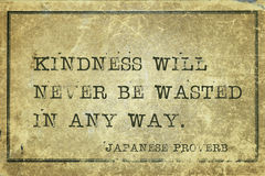 Kindness will JP. Kindness will never be wasted - ancient Japanese proverb printed on grunge vintage cardboard Royalty Free Stock Photo