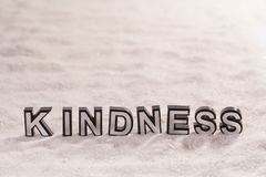 Kindness word on white sand. Kindness word silver and black on shiny white sand royalty free stock photography