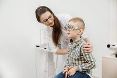 Kindontvangst de artsenoftalmoloog selecteert glazen van lens, het gezicht van het controleoog royalty-vrije stock afbeeldingen