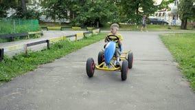 Kindritten op mobiele cyclus het kind drijft een auto Langzame Motie stock footage