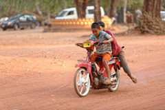 Kids on motorbike, Bakong Temple, Cambodia. Kids riding on motorbike along dirt road at Bakong Temple, Cambodia royalty free stock photography