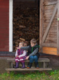 Kids sitting on the stair to an old shed Royalty Free Stock Photo