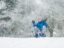 Kindspel in sneeuw met slee stock foto's
