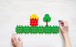 Kindspelen met de plastic ontwerper Handen van het kind en het beeld van het huis en de bomen Royalty-vrije Stock Fotografie
