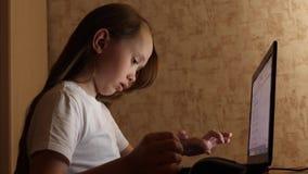 Kindspelen op computer in avond in de ruimte het jonge meisje doet haar thuiswerk op laptop meisjestypes in onderzoeksvraag op a stock videobeelden