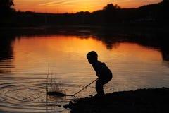 Kindspelen in water bij zonsondergang Royalty-vrije Stock Afbeelding