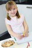 Kindtekening met kleurpotloden, zitting bij lijst in keuken Stock Foto