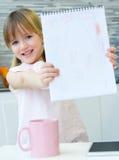 Kindtekening met kleurpotloden, zitting bij lijst in keuken Stock Afbeelding