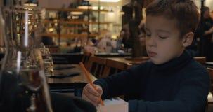 Kindtekening wanneer het zitten in koffie stock video